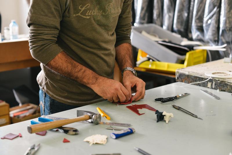 pessoa criando um produto com as maos em uma mesa com ferramentas com a transformacao digital na impressao 3d