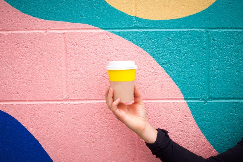 pessoa segurando um copo de café na frente de um muro colorido, aplicando o design thinking