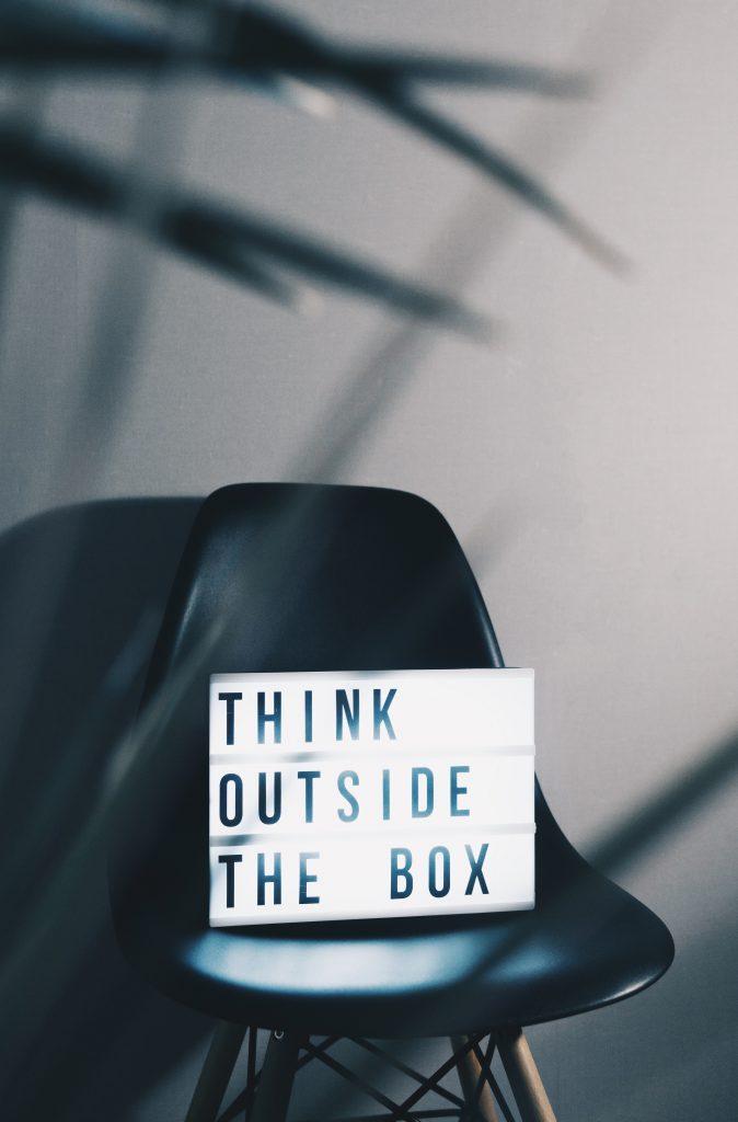 """cadeira com um letreiro luminoso: """"pense fora da caixa"""""""